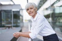 Portrait of confident senior woman leaning on railing in city — Stock Photo