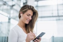 Mujer joven sonriente usando un teléfono celular en la oreja - foto de stock