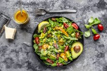 Salada com alface de cordeiro, tomate, abacate, molho de limão parmesão e curcuma — Fotografia de Stock