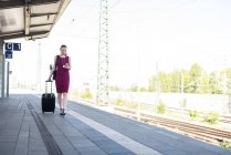 Mature businesswoman with smartphone and suitcase walking at platform — Stock Photo