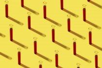 Fileira dos tubos de teste com líquido vermelho, fundo amarelo — Fotografia de Stock