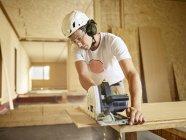 Arbeiter mit Helm sägt Holz mit Kreissäge — Stockfoto