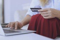 Частичное представление женщины за столом с кредитной картой и с помощью ноутбука — стоковое фото