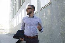 Empresário com celular andando na cidade — Fotografia de Stock