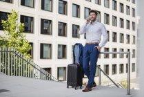 Geschäftsmann steht in der Stadt und telefoniert — Stockfoto