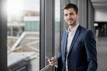 Ritratto di giovane uomo d'affari sorridente in un corridoio con cellulare e auricolari — Foto stock