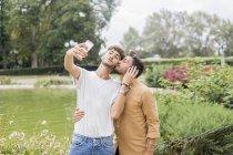 Счастливая молодая гей-пара делает селфи со смартфоном в городском парке — стоковое фото