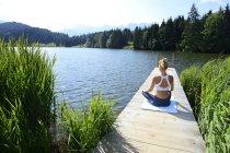 Германия, Миттенвальд, вид сзади женщины, занимающейся йогой на пристани у озера — стоковое фото