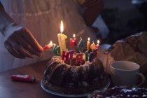 Woman lightning birthday cake candles, partial view — Stock Photo