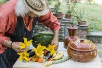 Старший мужчина украшает стол фруктами и овощами — стоковое фото