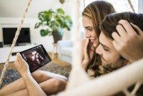 Счастливая влюбленная пара смотрит на ультразвук на планшете — стоковое фото