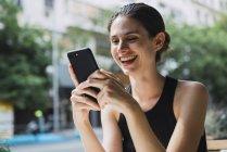 Jovem mulher rindo sentado na loja de cofee, usando smartphone — Fotografia de Stock