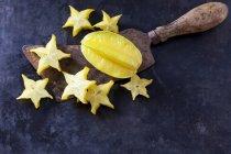 Нарезанный звездный фрукт на старом тесаке — стоковое фото