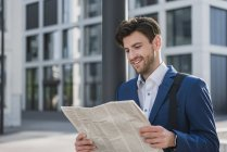 Smiling businessman reading newspaper in city — Stock Photo