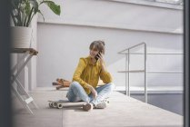 Young woman sitting on skateboard and talking on phone — Stock Photo