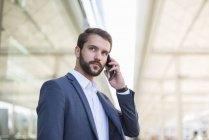 Giovane uomo d'affari sul cellulare guardando lateralmente — Foto stock