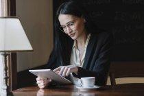 Улыбающаяся молодая деловая женщина с планшетом в кафе — стоковое фото
