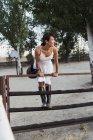 Ritratto di donna felice con casco pendente sul cancello del maneggio — Foto stock