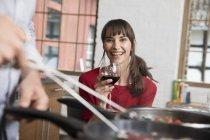 Женщина сидит на кухне, пьет красное вино, смотрит, как мужчина готовит еду — стоковое фото