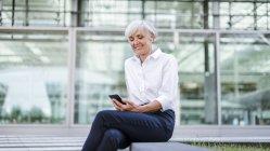 Empresária sênior sentada ao ar livre com smartphone e fones de ouvido — Fotografia de Stock