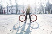 Молодий чоловік стоїть з велосипедом на міській площі. — стокове фото