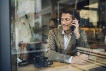 Uomo d'affari maturo seduto in caffetteria, a parlare al telefono — Foto stock