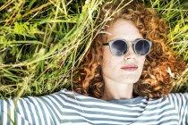 Primo piano della giovane donna che indossa occhiali da sole per rilassarsi sul prato — Foto stock