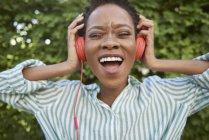 Retrato de mujer joven cantando con auriculares - foto de stock