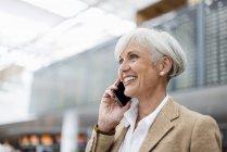 Una mujer de negocios sonriente en el teléfono celular en el aeropuerto - foto de stock