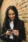 Souriant jeune femme utilisant un téléphone cellulaire au mur de briques — Photo de stock