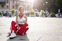 Усміхнена Дівчинка-підліток з винос напій сидить на міській площі на заході сонця — стокове фото
