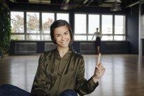 Усміхнена жінка сидить на підлозі в офісі — стокове фото