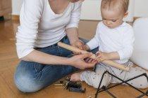 Mutter und Tochter bauen zu Hause einen Stuhl zusammen — Stockfoto