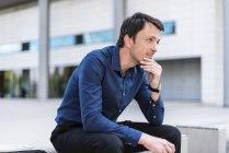 Empresario sentado al aire libre pensando - foto de stock