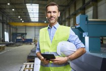Portrait of confident man wearing shirt and safety vest in factory — Stock Photo