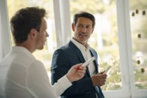 Mature businessman sharing his knowledge with younger colleague — Stock Photo