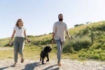 Junges Paar geht mit Hund auf dem Land spazieren — Stockfoto
