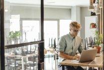 Молодой человек, работающий в стартап-кафе, используя ноутбук — стоковое фото