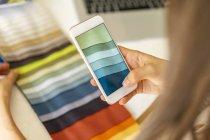 Designer de moda tirar fotos de amostras de tecido com ger telefone móvel — Fotografia de Stock