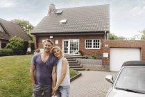 Портрет улыбающейся зрелой пары, стоящей перед домом — стоковое фото