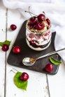 Стакан натурального йогурта с вишней, вишневым джемом и мюсли — стоковое фото