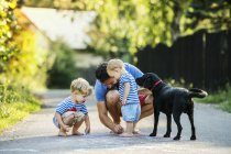 Man playing with his little children on the street in summer — Stock Photo