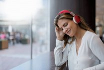 Smiling young woman listening to music with headphones — Stock Photo