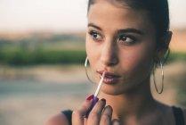 Portrait of teenage girl in nature applying lip gloss — Stock Photo