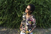 Улыбающаяся молодая женщина в солнечных очках и красочной блузке — стоковое фото