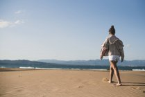 Back view of teenage girl walking on sandy beach — Stock Photo