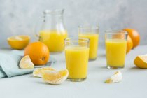 Glasses of freshly squeezed orange juice and orange slices — Stock Photo