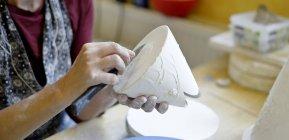 Gros plan sur une femme travaillant dans un atelier de porcelaine — Photo de stock