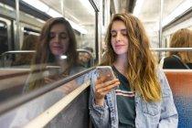 Sorridente giovane donna in treno sotterraneo guardando smartphone — Foto stock