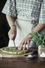 Mujer joven cortando garbanzos caseros y pastel de hierbas - foto de stock
